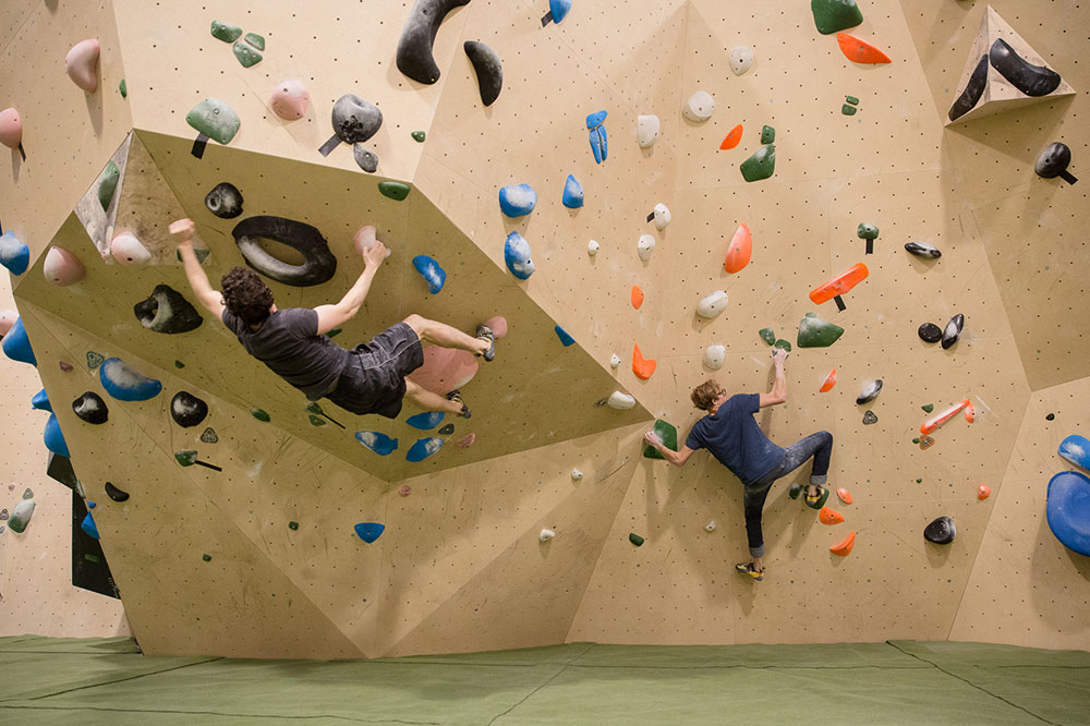 Two climbers using the cnc machined climbing wall at Yonder climbing centre. Both are in a dynamic stance on an overhanging technical section of the wall